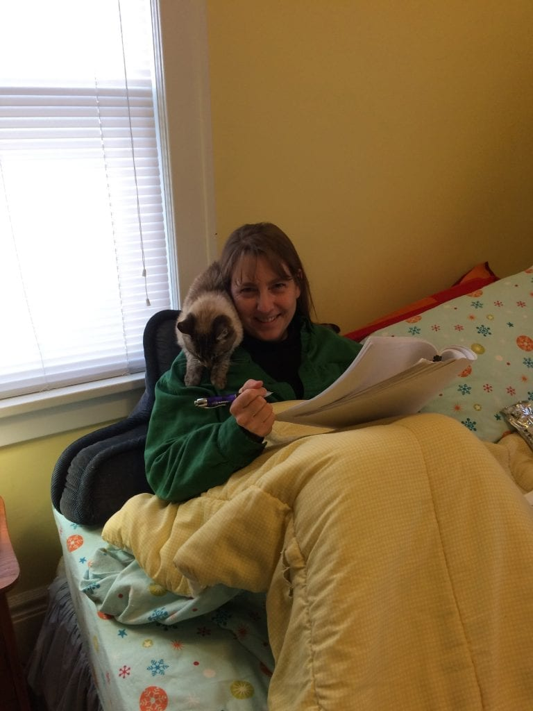 I have a very small house and don't have a separate office—so I often curl up in bed to work. My friendly at-home work coach (seen here on my shoulder) encourages me to keep writing.